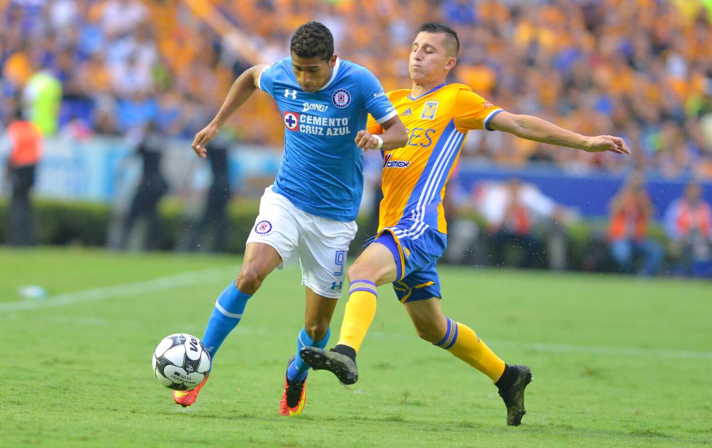 El jugador de Tigres, Francisco Torres (d), marca a Aldo Leao (i), de Cruz Azul, en partido entre felinos y La Máquina por la jornada 11 del Torneo Apertura del futbol mexicano, en el estadio Universitario de Monterrey, Nuevo León.