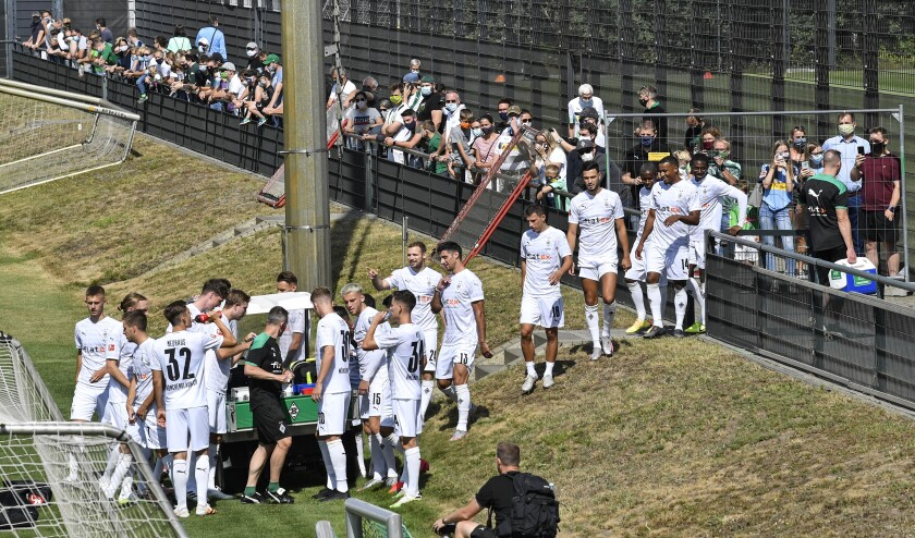 Borussia's team walks in front of their fans during the first training session of German Bundesliga club Borussia Moenchangladbach at the training ground in Moenchengladbach , Germany, Tuesday, Aug. 4, 2020. For the first time since the coronavirus outbreak, 300 supporters with face masks, online tickets and social distance were allowed to watch their team. (AP Photo/Martin Meissner)