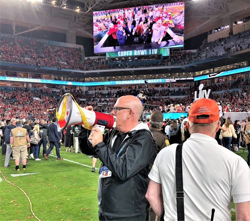 As field and audio team manager of Super Bowl LIV in Miami, San Diegan Bryan Ransom shouts instructions through a bullhorn to an army of workers setting up for the halftime show. His full-time job is directing San Diego State University's athletic bands.