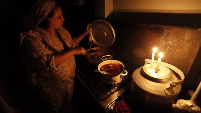 A woman prepares a meal in her kitchen during a power outage in Peshawar, Pakistan, on May 24, 2017.