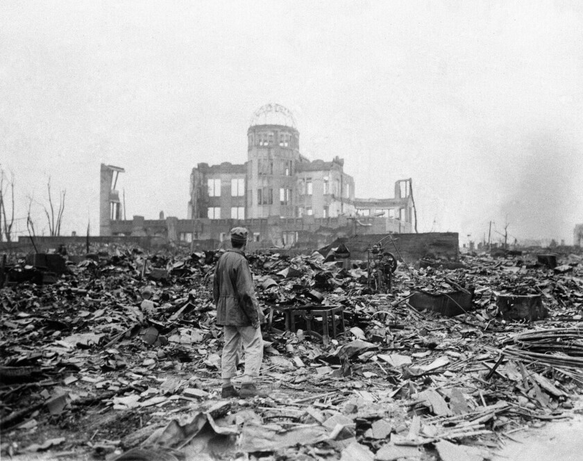 In this Sept. 8, 1945 file photo, an allied correspondent stands in the rubble in front of the shell of a building that once was a movie theater in Hiroshima, Japan, a month after the first atomic bomb ever used in warfare was dropped by the U.S.