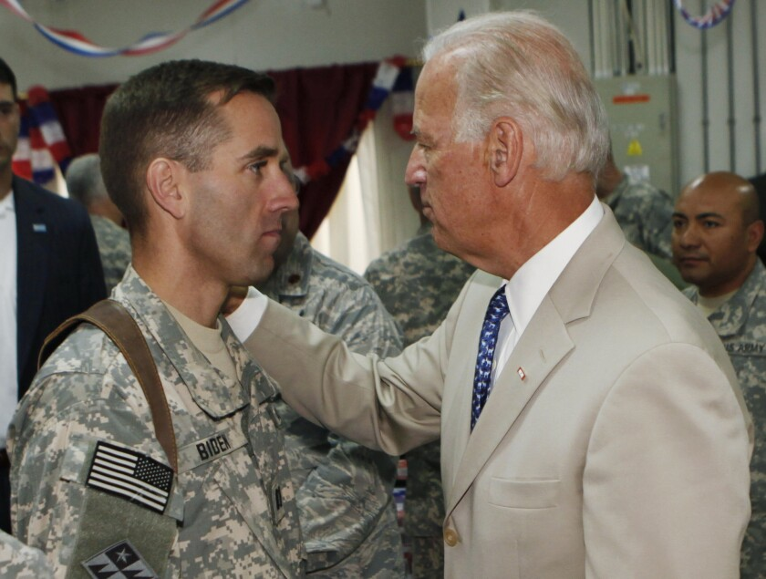 Vice President Joe Biden, right, talks with his son, U.S. Army Capt. Beau Biden, at Camp Victory on the outskirts of Baghdad, Iraq in 2009.