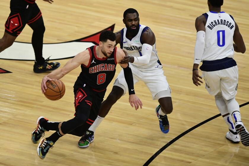 Chicago Bulls' Zach LaVine (8) drives against Dallas Mavericks' Tim Hardaway Jr. (11) during the first half of an NBA basketball game Sunday, Jan. 3, 2021, in Chicago. (AP Photo/Paul Beaty)