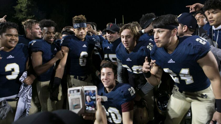 Mater Dei Catholic players savor their Division II championship after defeating Olympian.