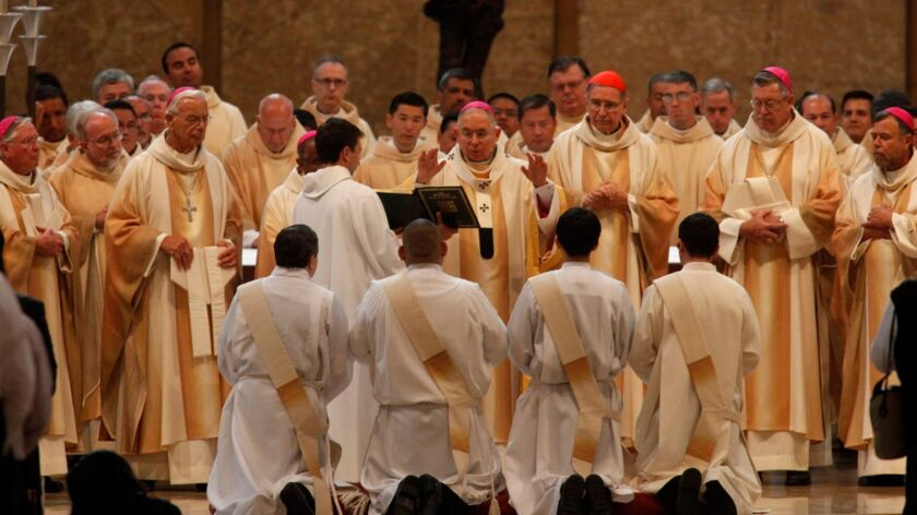 Los Angeles Archbishop Jose H. Gomez says a prayer over new Catholic priests during their ordination in 2014. The number of priests has dropped by more than 30% in the U.S. since 1965..