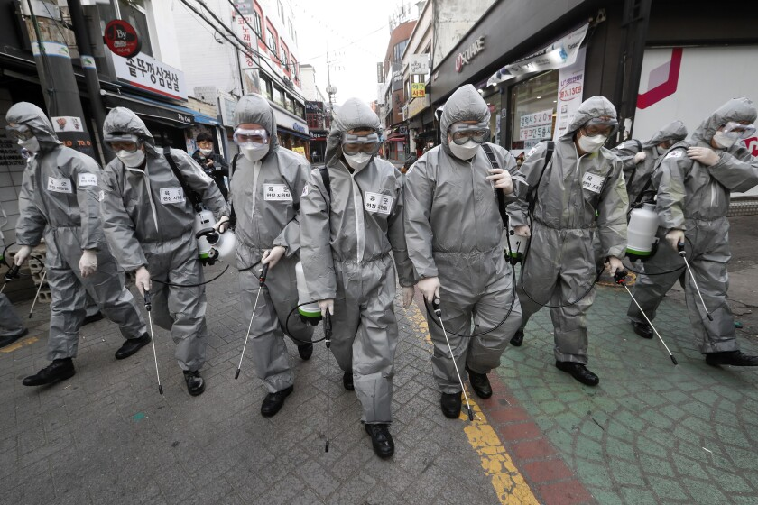 Army soldiers wearing protective suits spray disinfectant as a precaution against the new coronavirus at a shopping street in Seoul, South Korea, Wednesday, March 4, 2020. The coronavirus epidemic shifted increasingly westward toward the Middle East, Europe and the United States on Tuesday, with governments taking emergency steps to ease shortages of masks and other supplies for front-line doctors and nurses. (AP Photo/Ahn Young-joon)