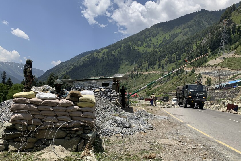 Paramilitary soldiers keep guard as an Indian army convoy moves on the Srinagar-Ladakh highway in northern India.