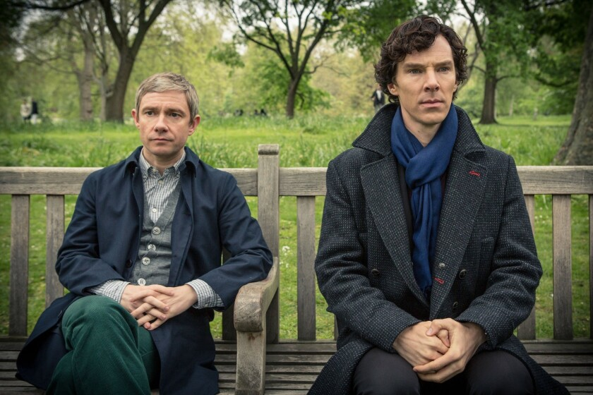 "Martin Freeman, left, as Dr. Watson, and Benedict Cumberbatch, as Holmes, sitting on a bench in ""Sherlock."""