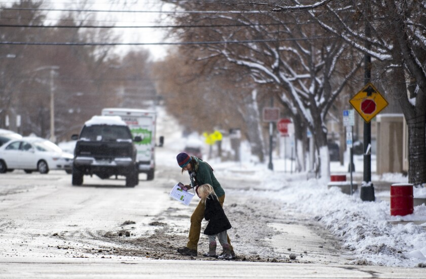 A woman and child cross the street on a windy and snowy morning in Greeley, Colo.