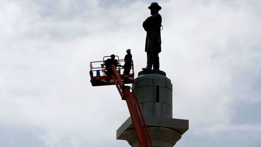 Workers prepare to take down the statue of Robert E. Lee, former president of the Confederacy, which