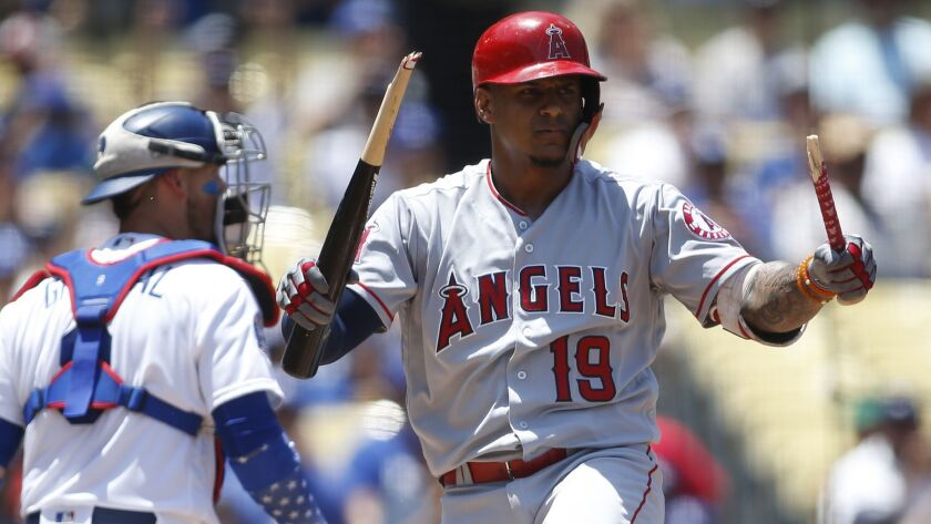 Los Angeles Angels Jefry Marte, right, breaks his bat over his leg after striking out on a full coun