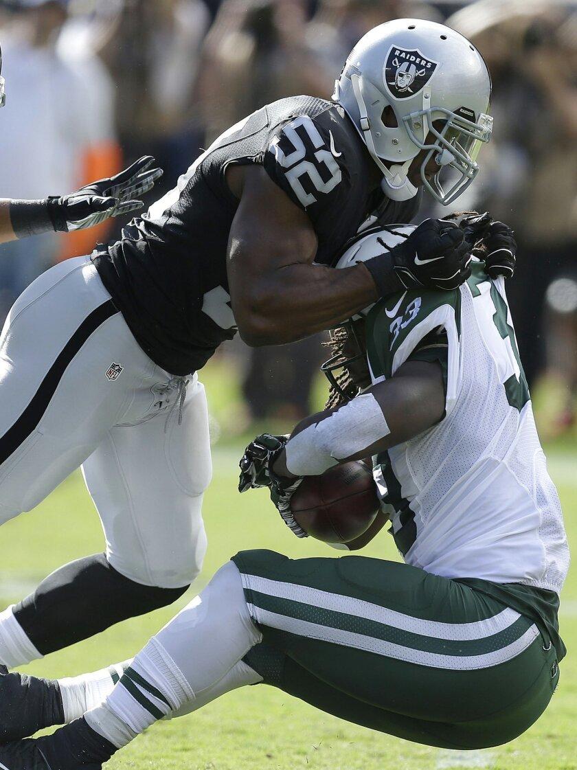 Oakland Raiders outside linebacker Khalil Mack (52) tackles New York Jets running back Chris Ivory during the first half of an NFL football game in Oakland, Calif., Sunday, Nov. 1, 2015. (AP Photo/Ben Margot)