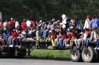 Un grup de migrants viatja a la plataforma d'un camió per una carretera de Santa Rosa de Copán, Hondures, el divendres 15 de gener de 2021, amb l'esperança d'arribar als Estats Units. (AP Fotografia / Delmer Martínez)