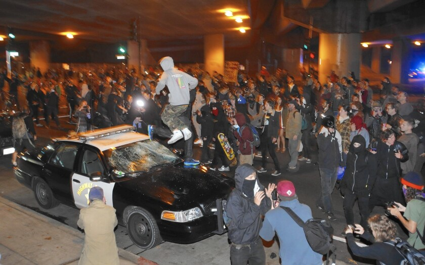 A man jumps on a vandalized California Highway Patrol squad car in Oakland on Sunday during another night of demonstrations.