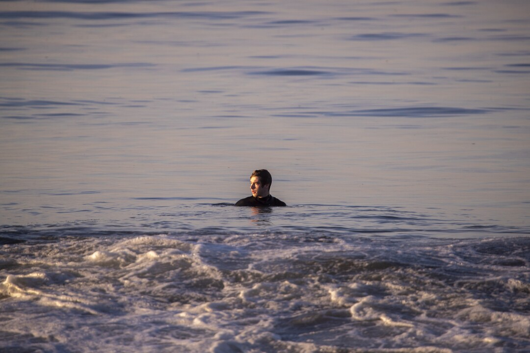 An oil slick lines the beach as a swimmer comes in after being called in by a Newport Beach lifeguard.