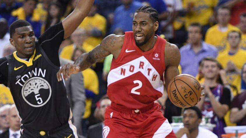 Toronto Raptors forward Kawhi Leonard drives past Golden State Warriors center Kevon Looney during Game 6 of the NBA Finals on June 13.