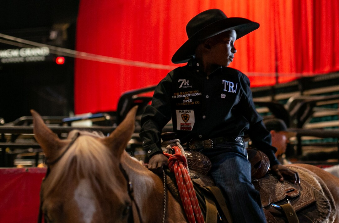 A young cowboy sits on his horse