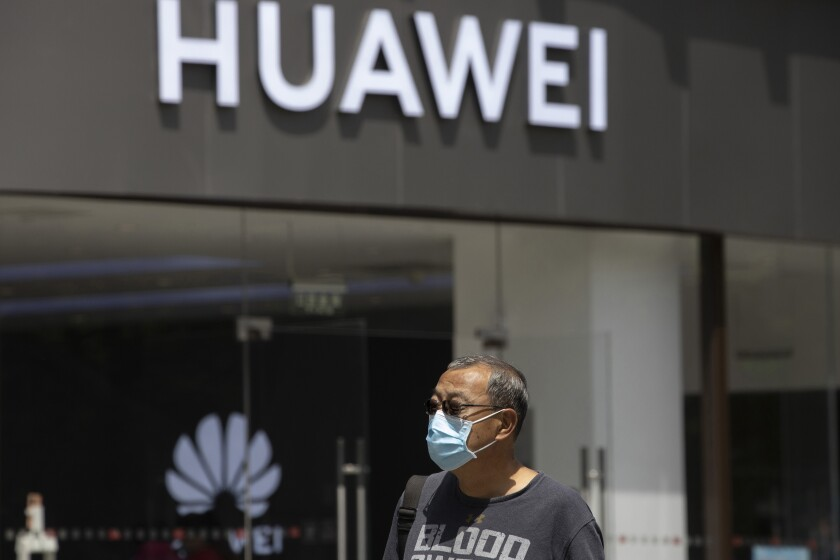 """FILE - In this May 18, 2020, file photo, a man wearing a face mask to protect against the coronavirus walks past a Huawei retail store in Beijing. One of China's biggest tech companies has criticized the Trump administration for """"politicizing business"""" after it slapped export sanctions on 33 more Chinese enterprises and government entities. The announcement expanded a U.S. campaign against Chinese companies Washington says might be security threats or involved in human rights abuses. Beijing criticized curbs imposed earlier on tech giant Huawei and other Chinese companies but has yet to say whether it will retaliate. (AP Photo/Ng Han Guan, File)"""