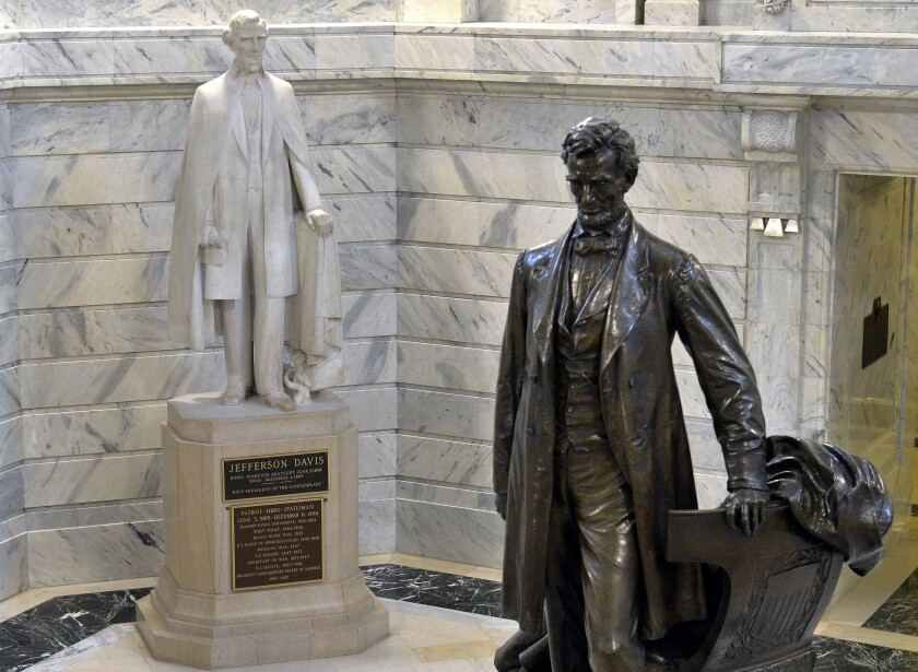 A statue of Jefferson Davis, left, faces a statue of Abraham Lincoln in the Rotunda of the state Capitol in Frankfort, Ky.