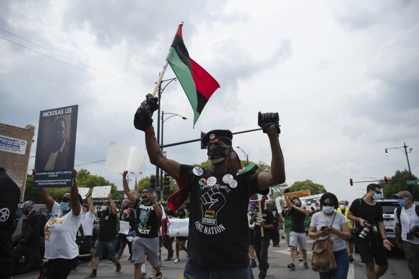 About 200 anti-police brutality protesters march in the neighborhood of Bronzeville, in Chicago, Saturday, Aug. 15, 2020. Protesters walked from Bronzeville to Grant Park, after police prohibited them from marching along the Dan Ryan Expressway. (Pat Nabong/Chicago Sun-Times via AP)