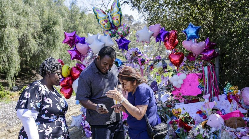 Anthony Jones shares some memories of daughter Trinity Jones on his phone with Mary Montes at a makeshift memorial in Hacienda Heights where the girl's body was discovered. Barbara Jones, the girl's grandmother, is at left.