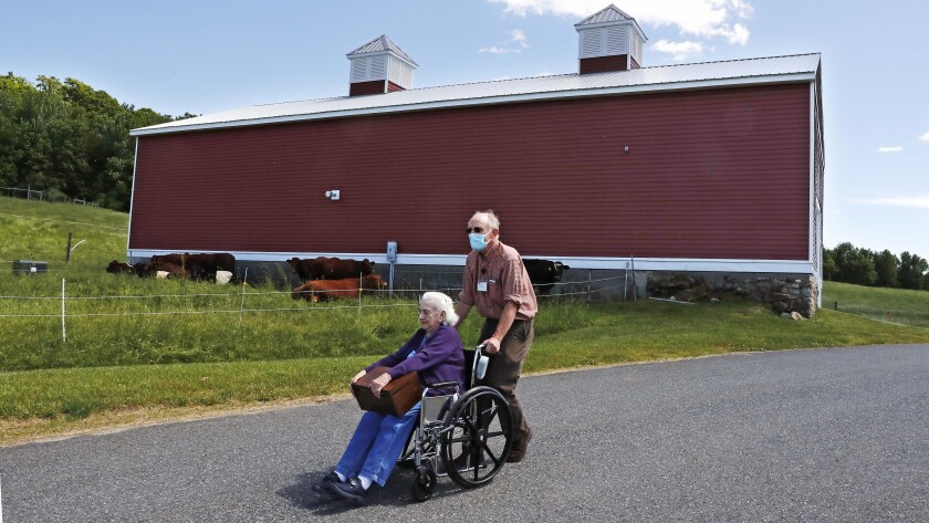 In this Monday, June 8, 2020, photo, 93-year-old Flo Young, originally from Cambridge, Mass., holds a box of pen pal letters as she takes a ride past a barn with activity aide Rich Vanderweit outside the Sullivan County Health Care nursing home in Unity, N.H. In a letter-writing effort during the virus pandemic to connect nursing home residents in two neighboring communities, residents now are receiving pen pal letters from across the United States. (AP Photo/Charles Krupa)