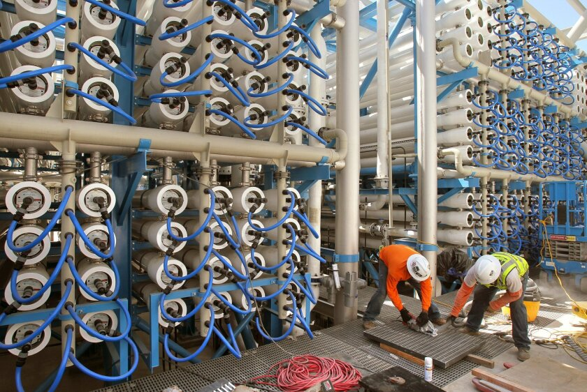 Workers prepare some of the 1,700 reverse osmosis vessels at the new Carlsbad Desalination Project Thursday. The San Diego County Water Authority says the state should give the region credit for the project, and others that build capacity, in conservation calculations.