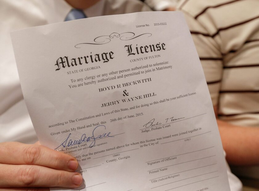 Boyd Beckwith holds his marriage license with his soon-to-be spouse Jerry Hill during a mass wedding ceremony in Atlanta on Friday.