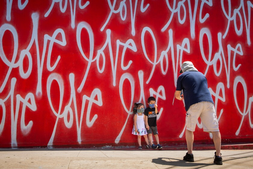 Tom Sean Foley takes a photo of his children in front of a mural in Culver City