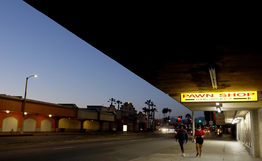 Women wearing masks walk along Van Nuys Boulevard in Panorama City on Saturday.