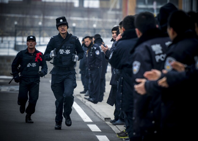 Two SWAT policemen run during a training competition in Urumqi in northwest China's Xinjiang region, where tension between law enforcement and Muslim Uighurs runs high.