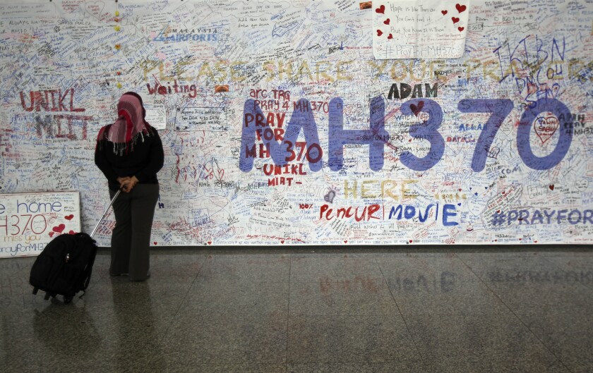A woman reads messages for passengers aboard a missing Malaysia Airlines plane at Kuala Lumpur International Airport in Sepang, Malaysia, on Tuesday.