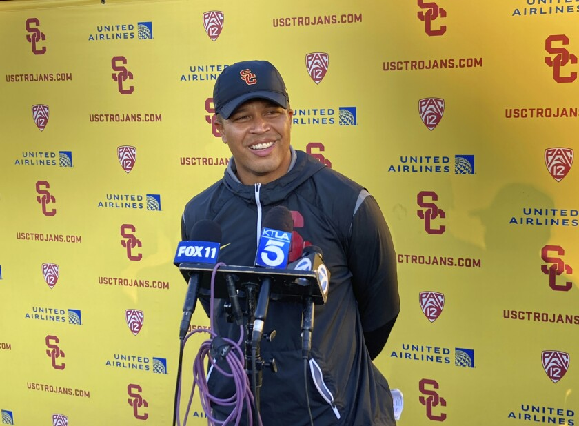USC interim head football coach Donte Williams smiles while answering questions after practice.