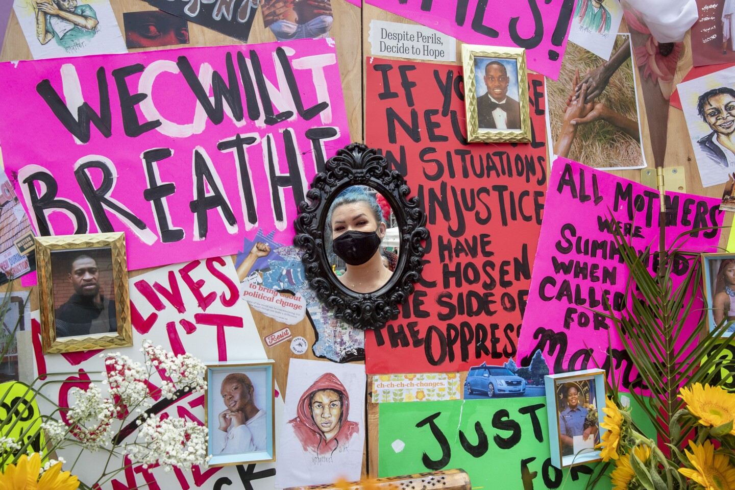 """LEIMERT PARK, CA - JUNE 19: Sierra Hood of Big Bear Lake is reflected in a mirror on her """"Pray for the Hood"""" altar on the corner of 43rd Street and Degnan Blvd. during Juneteenth celebration on Friday, June 19, 2020 in Leimert Park, CA. The alter was set up to reflect, heal and say a prayer. (Brian van der Brug / Los Angeles Times)"""