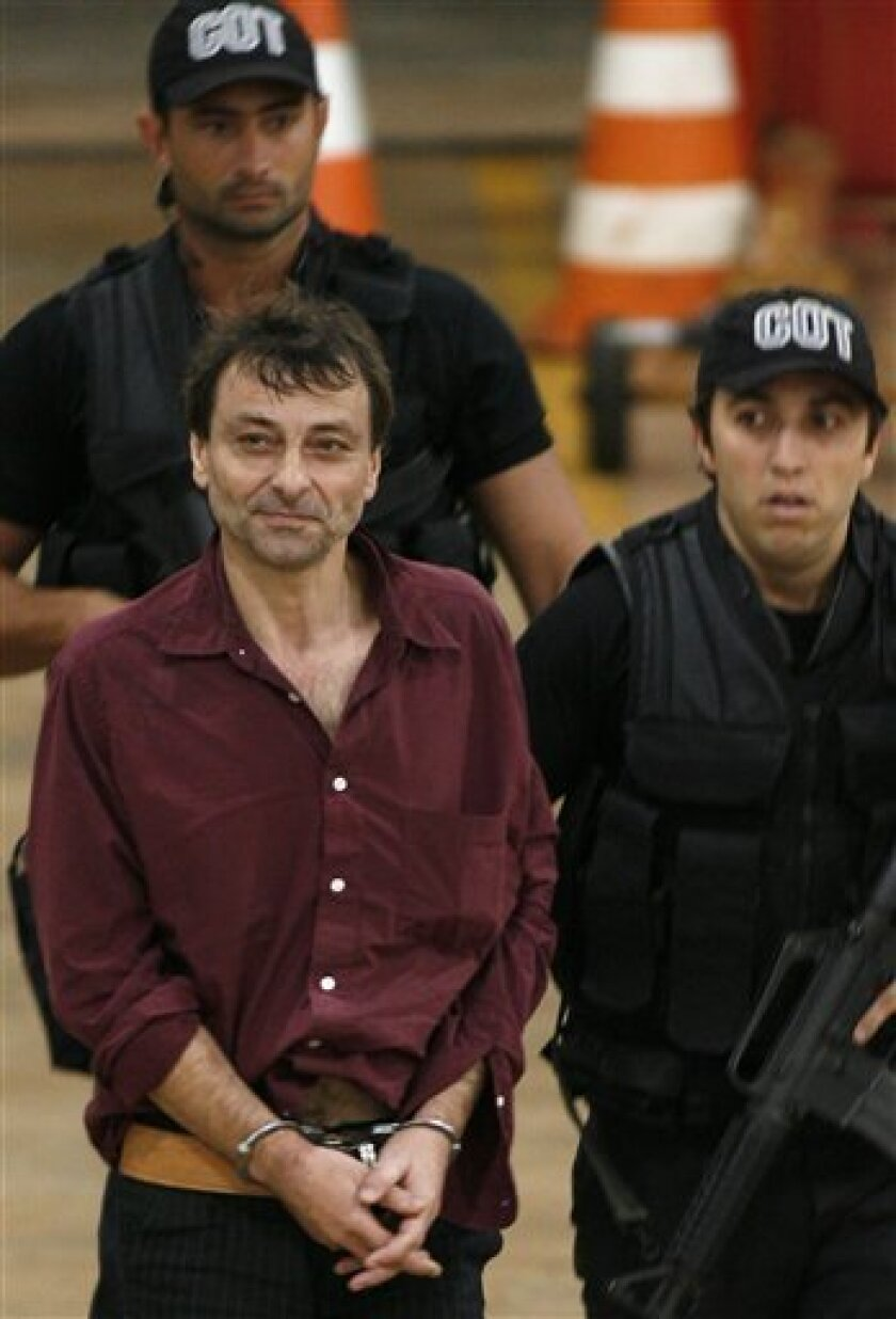 Leftist Italian activist Cesare Battisti is escorted by Brazilian Federal Police officers as he arrives at the Brasilia's airport in this March 19, 2007 file photo. Battisti escaped from an Italian prison in 1981 while awaiting trial on four counts of murder allegedly committed when he was a memb