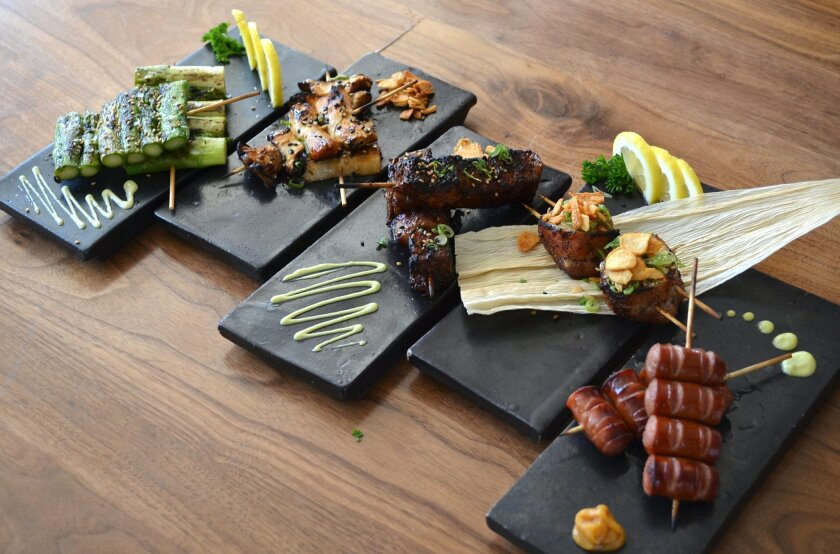 A selection of robata at newly opened Blue Ocean Robata & Sushi in Carlsbad. The charcoal-grilled snacks include, asparagus spears, left, king oyster mushrooms, pork belly cubes, bacon-wrapped scallops and Kurobuta sausage.