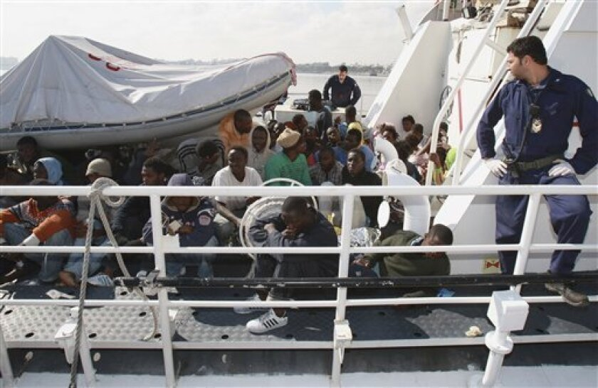 FILE - In this Thursday, May 7, 2009 file photo, rescued migrants are seen on board an Italian coast guard boat while arriving at the port of Tripoli, Libya after Italy shipped more than 200 migrants who had been rescued in the Mediterranean Sea back to Libya. The U.N. refugee agency UNHCR said Tuesday, June 8, 2010 that it is being expelled from Libya without explanation despite being responsible for registering thousands of refugees in the North African country. (AP Photo/Abdel Magid al-Fergany, File)