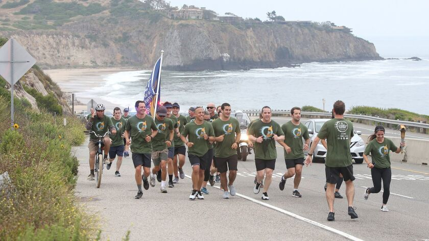 Laguna Beach Police officers and lifeguards run up Coast Highway past Crystal Cove as they do their