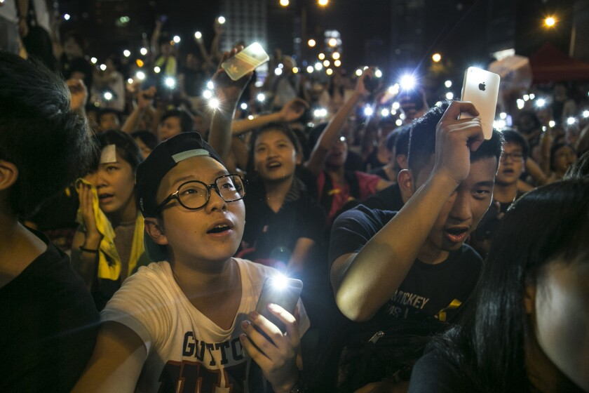 Student protesters hold their cell phone lights while chanting pro democracy slogans at the protest site in Hong Kong.