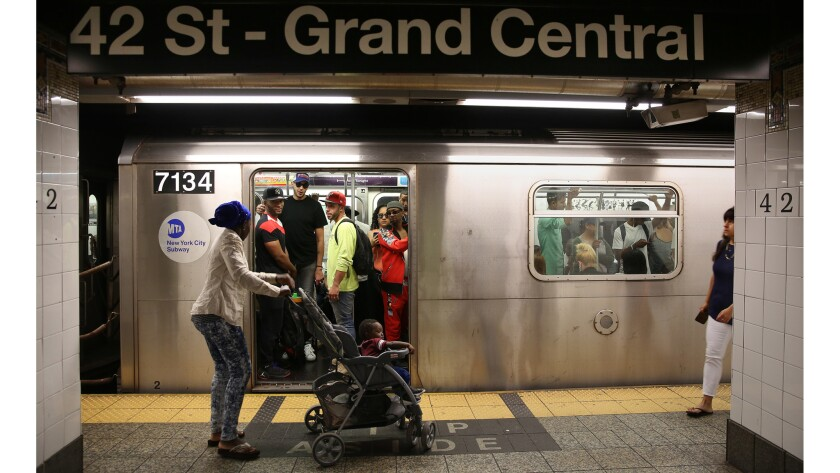 A woman with a baby stroller waits to get on a train at Grand Central Terminal.