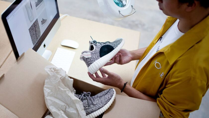 A GOAT authentication specialist verifies a pair of Yeezy sneakers.