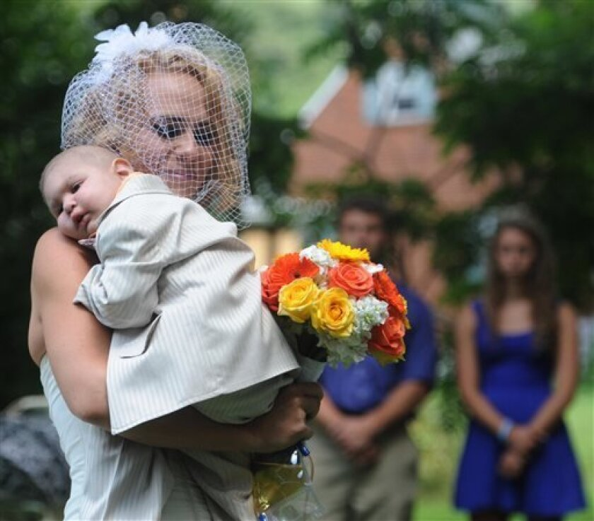 FILE - This Aug. 3, 2013 file photo, Christine Swidorsky carries her son and the couple's best man, Logan Stevenson, 2, down the aisle to her husband-to-be Sean Stevenson during the wedding ceremony in Jeannette, Pa. Christine Swidorsky Stevenson says on her Facebook page that Logan died in her arms at 8:18 p.m. Monday, Aug. 5, 2013, at their home in Jeannette, about 25 miles east of Pittsburgh. Logan, who was born Oct. 22, 2010, was diagnosed shortly after his first birthday with acute myelo