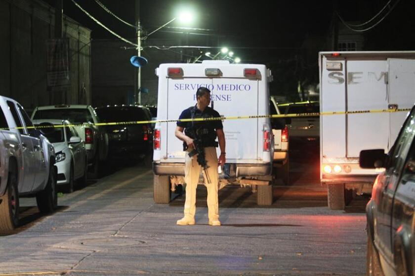 Fotografía de archivo del 22 de marzo de 2018 que muestra a un policía custodiando el sitio donde unas ocho personas resultaron muertas y otras 11 heridas, tras un ataque de un grupo armado en el municipio de Purísima del Rincón, en el estado de Guanajuato (México). EFE/Archivo