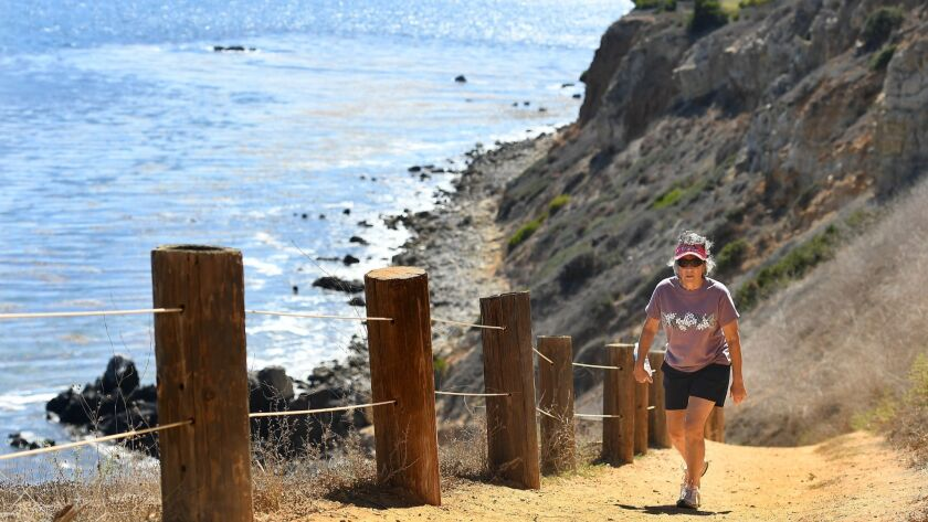 Maureen Sassoon walks up a hiking pass near Terranea in Rancho Palos Verdes. In Southern California, cliffs could recede more than 130 feet by the year 2100 if the sea keeps rising, according to a new study.