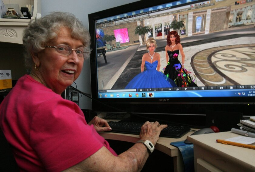 Fran Swenson is nimble on the keyboards as she interacts her virtual character Fran Seranade, in blue dress, with Barbara Alchemi, her daughter's character, in an online virtual reality world called Second Life. photo by Bill Wechter
