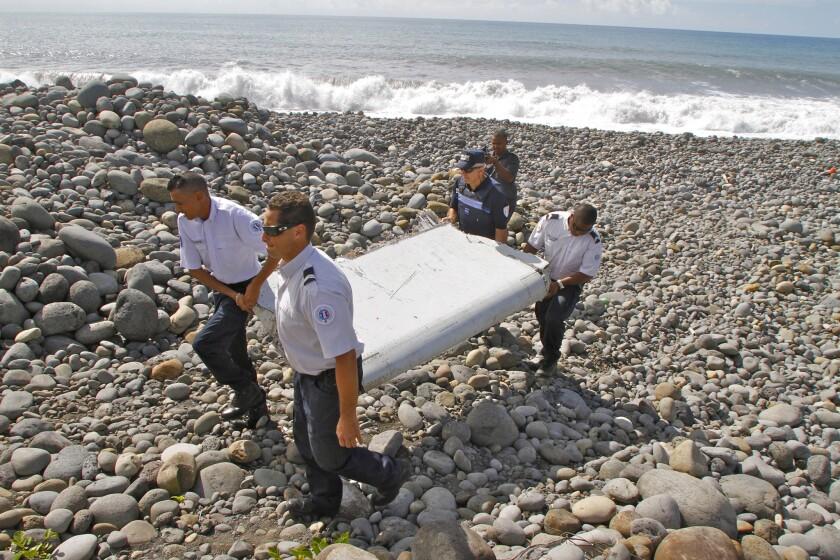 Policías franceses cargan una pieza de un avión encontrada en el municipio de Saint-André, en la isla Reunión, el 29 de julio de 2015. Esta pieza podría ser la primera pista del vuelo 370 de Malaysia Airlines desde su desaparición hace casi año y medio con 239 personas a bordo. (Foto AP/Lucas Marie)