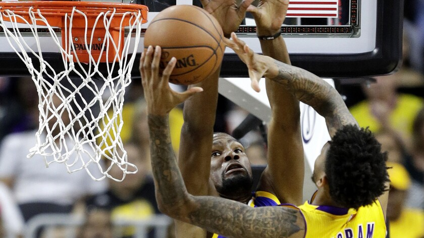 Lakers forward Brandon Ingram tries to score at the rim against Warriors forward Kevin Durant during a preseason game on Saturday night in Las Vegas.