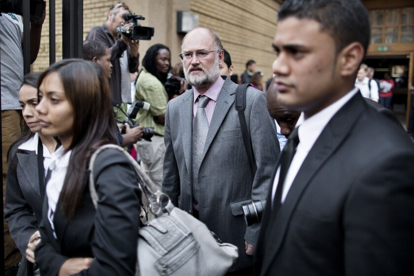 Forensic geologist Roger Dixon, center, leaves court in Pretoria, South Africa, after testifying in the trial of Olympic athlete Oscar Pistorius.