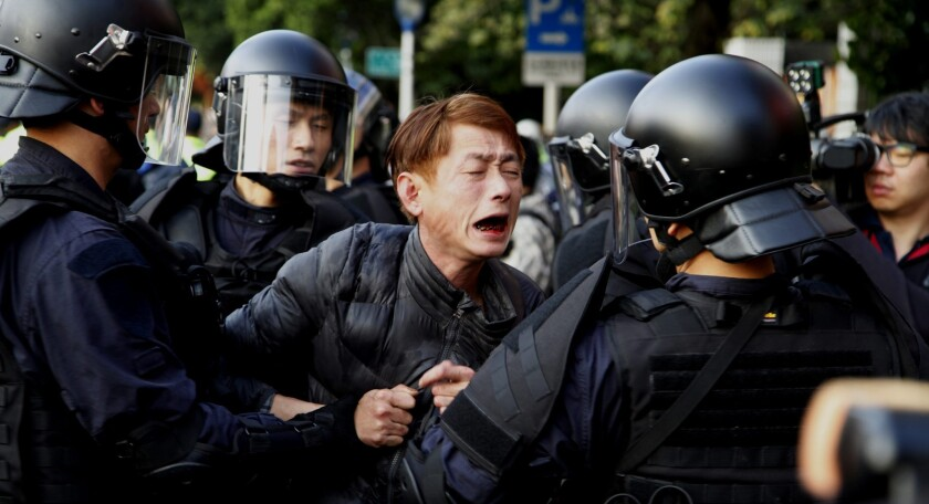 Riot police detain a protester near Taiwan's Cabinet compound in Taipei. Demonstrators opposed to a trade deal with Beijing had forced their way into the compound.
