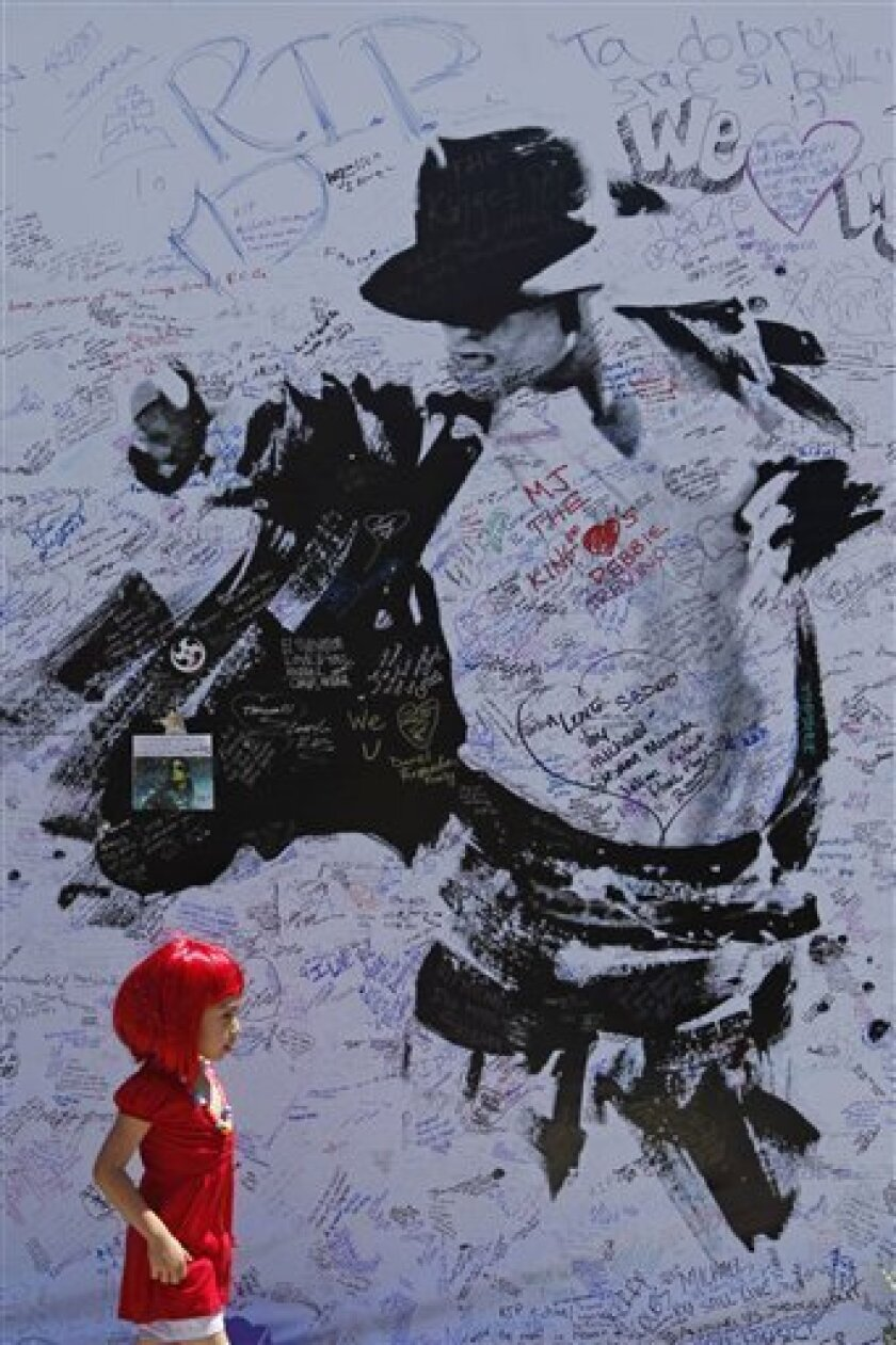 A child passes a large poster at the Staples Center in Los Angeles , Sunday, July 5, 2009. The venue is the planned location for late pop star Michael Jackson's memorial service scheduled for Tuesday, July 7. (AP Photo/Matt Rourke)